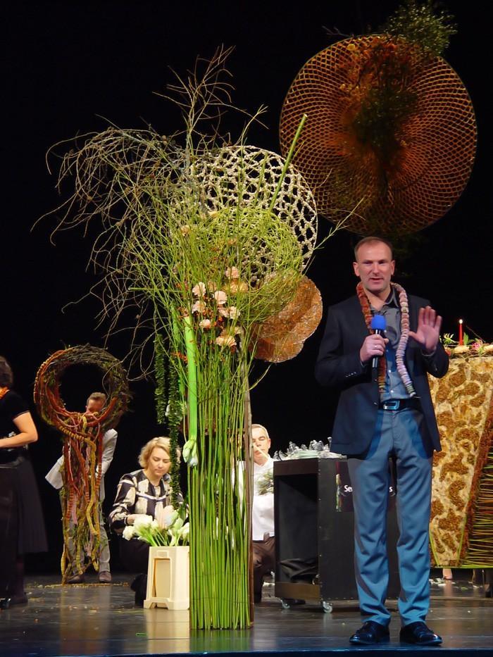 Praca Inny Petrenko i Marijus Gvildys z girlandą z chryzantem.